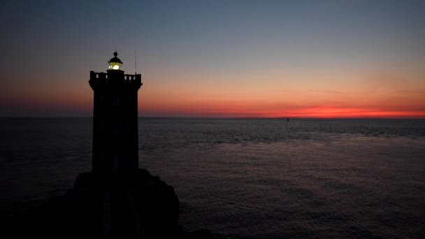 silhouette of lighthouse building in sunset marine scene