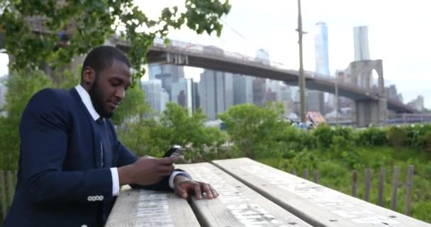 Young businessman in suit talking on smartpone while standing on background of Brooklyn Bridge  , New York City
