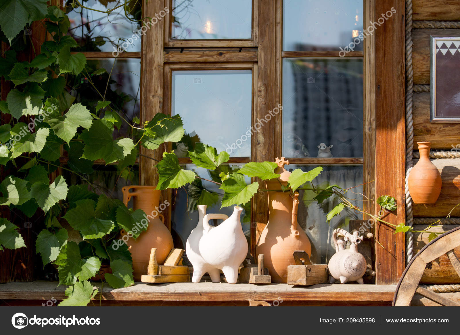 Clay brown pots in front of the window of a wooden house. Wooden house and  decor in front of the house. 12