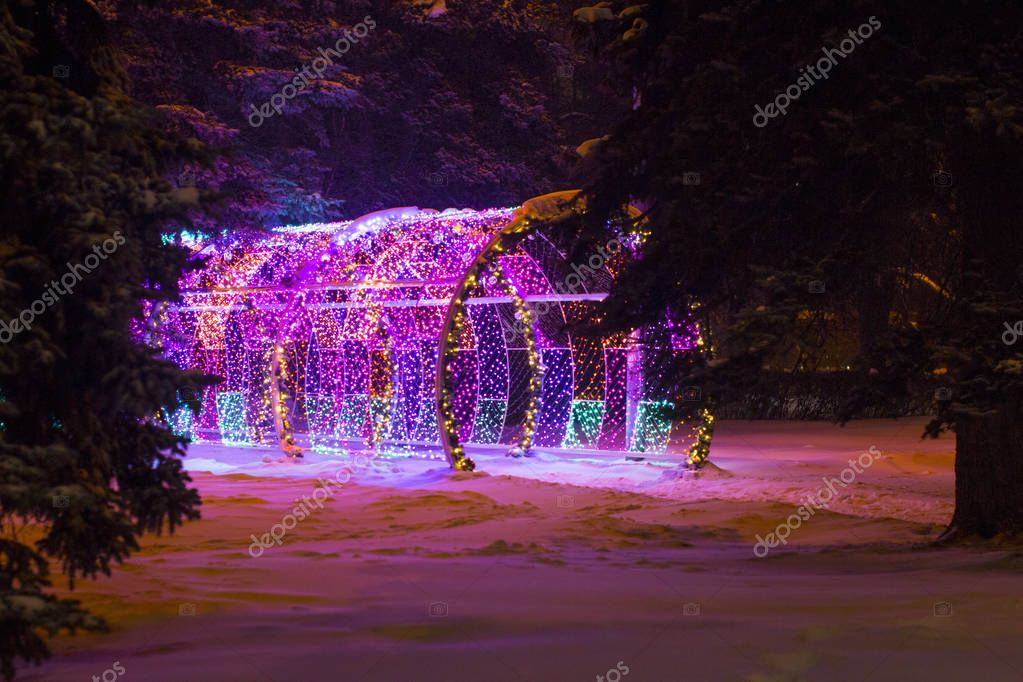 Outdoor holiday light tunnel. Tunnel with colored light bulbs. Winter evening.