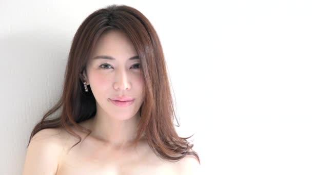 Skutečné asijských lidí portrét s emoce a pocity. Detail hezkou tvář na bílém pozadí. Krásná mladá Japonka usměvavý, smyslná dívka při pohledu kamery a zobrazení ženské krásy