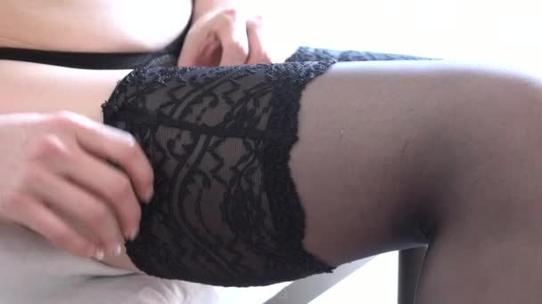 Beautiful young Japanese woman wearing lingerie. Sensual girl showing female beauty and putting on sexy black stockings