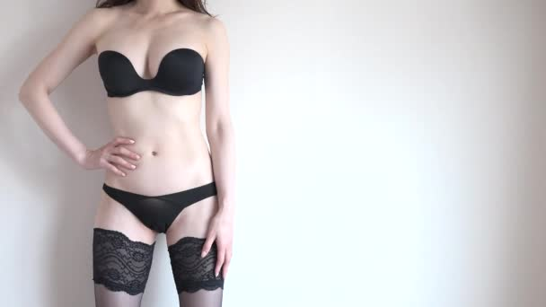 Beautiful young Japanese woman wearing lingerie. Sensual girl showing female beauty with bra, panties and stockings. Cropped body and copy space