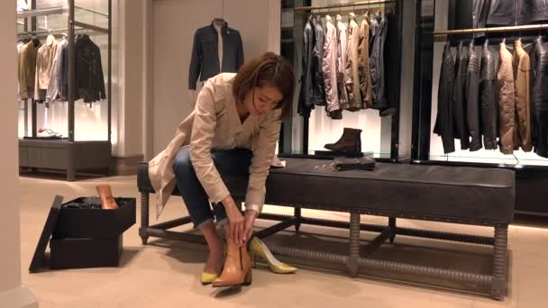 Asijské lidé Nákupy módního zboží a doplňků. Japonská žena v luxusní obchod uvnitř obchoďáku. Lady kupovat nové boty v obchodě a mluví na manažera prodeje pro nápovědu a pomoc
