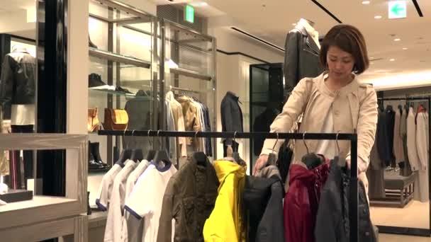 Asijské lidé Nákupy módního zboží a doplňků. Japonská žena v luxusní obchod uvnitř obchoďáku. Matka nákup dětské bundy v obchodě a mluví s prodejní asistent pro nápovědu a pomoc