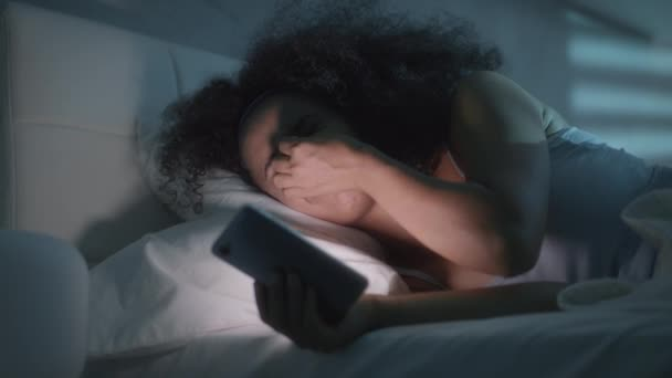 Young African American Woman Texting With Smartphone In Bed