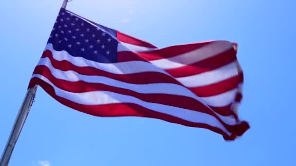 American Flag flying with sun and sky in the background. Stars and Stripes of the United States of America, symbol and concept of freedom, liberty, democracy. Copy space