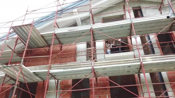 Architect and women in construction site. Man with female clients buying new home. Gay people looking at new apartment in building with scaffolding. Drone shot