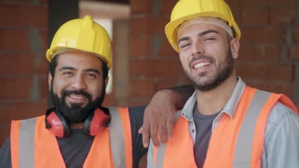 People working in construction site. Portrait of happy men at work in new house inside apartment building. Professional workers looking and smiling at camera as co-workers and friends. Slow motion.