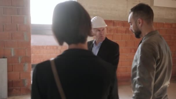 Handelsvertreter im Gespräch mit Kunden im neuen Gebäude. Mann arbeitet als Makler in Baustelle mit Kunden. Immobilien Makler zeigen Heimat von Mann und Frau. Junges Paar als Käufer des neuen Hauses
