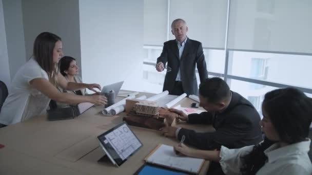 Podnikatel mluví do skupiny podnikatelů během firemní setkání