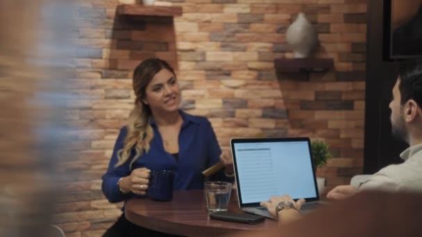 Mladí hosté muž a žena pracující v kanceláři jídelny. Latino podnikatel a obchodnice na firemní pracoviště. Zaneprázdněn hispánský správce a spolupracovníky pomocí počítače v práci. Zaměstnanci a kolegové