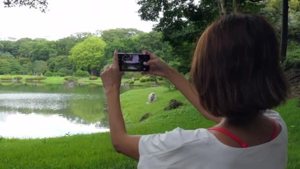 Asiatin fotografiert mit Smartphone im Stadtpark. Japanerin fotografiert mit Handy im Freien. Mensch und Technik