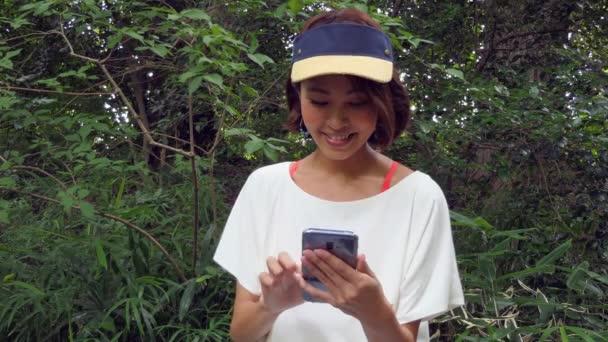 Asijská žena, která používá smartphone pro Internet a e-mail v městském parku. Šťastná Japonská dáma drží mobil venku. Lidé a technika