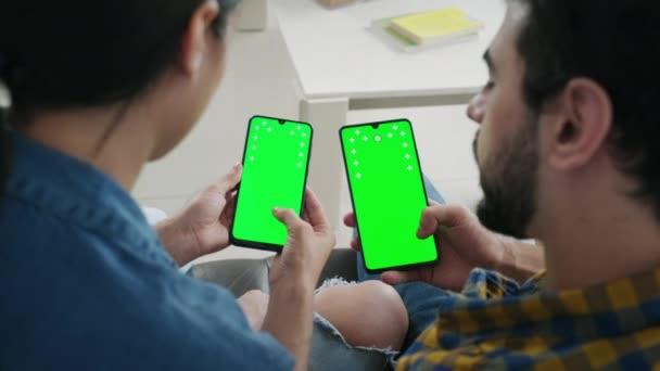 Mladí lidé používají mobilní telefony se zelenou obrazovkou pro internet a sociální média. Muž a žena držící smartphony pro webové stránky. Přítel a přítelkyně sledující film a fotografie na mobilních telefonech