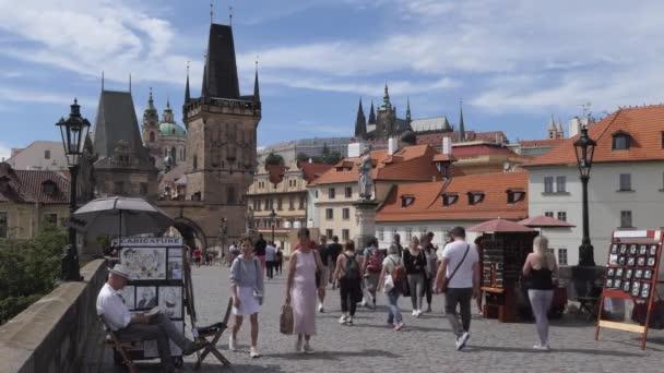 PRAHA / ČESKÁ REPUBLIKA - červen 2020: Pohled na Karlův most, historický most a turistickou památku na řece Vltavě (Moldau) v Praze, Česká republika, Evropa. Městská krajina s lidmi chůze, turisté navštíví město