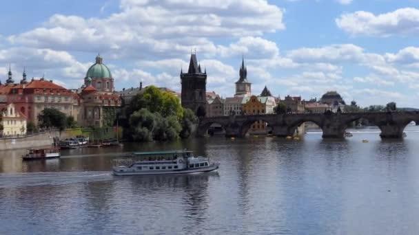 PRAHA / ČESKÁ REPUBLIKA - červen 2020: Pohled na Karlův most, turistická atrakce na řece Vltavě v Praze, Česká republika, Evropa. Městská krajina s přívozními čluny památník a stará budova