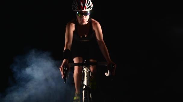Mosolygós nő kerékpározás road bike, Pedálozás kerékpár, sport koncepció, stúdió fekete