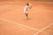 Photo old-fashioned tennis player training with wooden racket on brown court