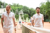 Fotografie athletic tennis players with wooden rackets walking near net on court