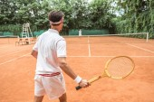 Fotografie back view of sportsman playing tennis with wooden racket on tennis court