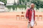 hezký kavkazské tenista s raketou stojící na net na tenisový kurt