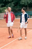 Fotografie fröhliche sportliche Freunde mit hölzernen Schläger gehen auf Tennisplatz