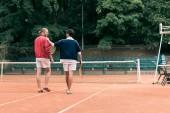 Fotografie Heckansicht des altmodischen Freunde mit hölzernen Schläger gehen auf Tennisplatz
