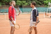 men with wooden rackets conflicting on tennis court