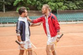 angry sportsmen with wooden rackets conflicting on tennis court