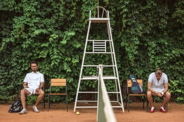 tennis players resting after training on chairs on court