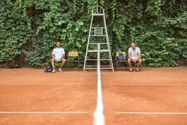 retro styled tennis players resting after training on chairs on brown court