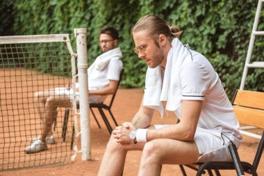 upset tennis players resting on chairs on court