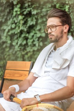 tired old-fashioned tennis player with towel and tennis racket resting on chair on tennis court