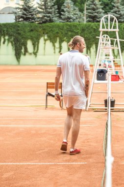 rear view of tennis player with racket on tennis court