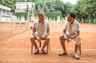 handsome smiling tennis players with wooden rackets resting on chairs