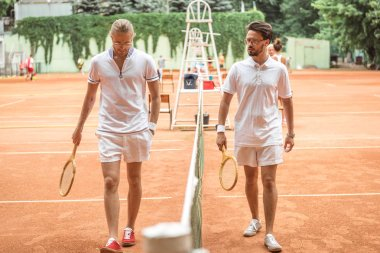 tennis players with wooden rackets walking near net on court