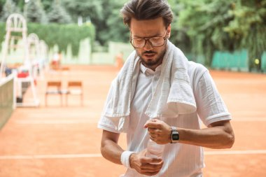 handsome tennis player with towel and bottle of water on tennis court