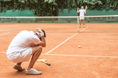 frustrated tennis player after fail on brown tennis court