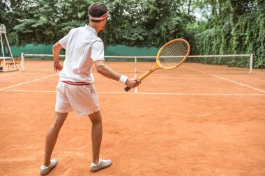 back view of tennis player with retro wooden racket on tennis court