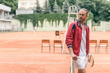handsome caucasian tennis player with racket standing at net on tennis court