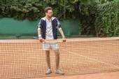 hezký tenista retro raketa stál na net na tenisový kurt
