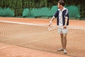 Photo athletic tennis player with wooden racket leaning on tennis net on court