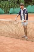 szép retro sportember, támaszkodva a tenisz háló barna bíróság ütő