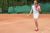 pohledný muž v sportovní retro dřevěnou raketou na tenisový kurt