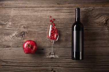 Ripe pomegranate fruit with a glass of wine, a bottle on a wooden background. Top view with copy space.