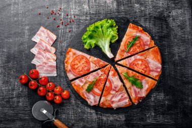Traditional italian pizza with mozzarella cheese, ham, tomatoes, pepper, pepperoni spices and fresh rucola on a stone and a black scratched chalk board. Top view.