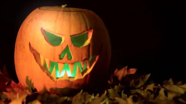 Kísérteties Jack Olantern halloween tök száraz leveleken.Változó színe a fény belsejében. Fekete háttér és másolótér