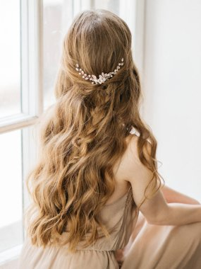 Portrait with natural light of pretty young woman with beautiful hairstyle decorated by stylish hair accessory, rear view