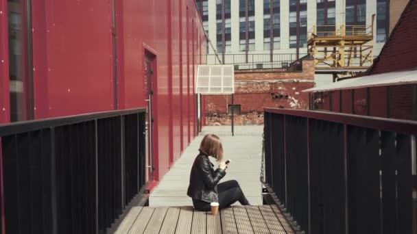 Junge Frau sitzt auf der Treppe und blättert durch ihre Nachrichten feed auf Smartphone mit Tasse Kaffee